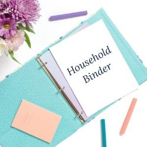 blue Household Binder laying flat on a white table with flowers and 3 pens