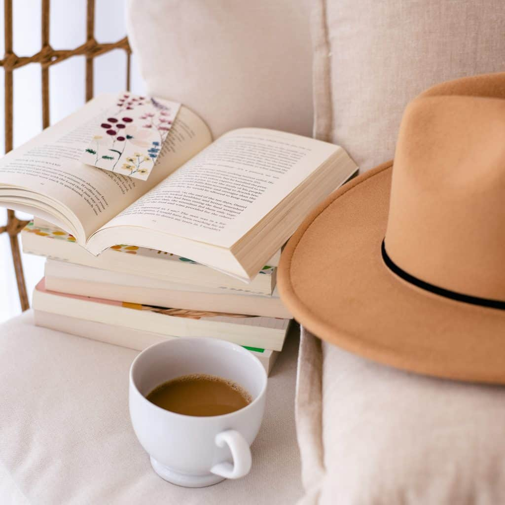 comfy chair with a pile of books, a cup of coffee and a hat - Time for You, time for a good book - take time to read