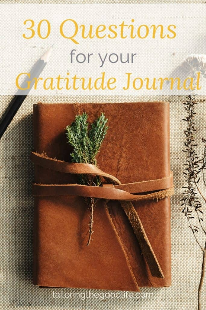 leather journal on canvas back ground with a pencil and some twigs ready for gratitude journal prompts