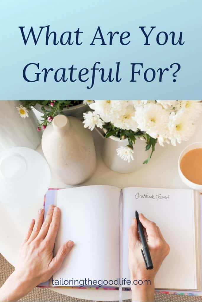 open gratitude journal on round white table with flowers and a cup of tea to work on gratitude journal prompts