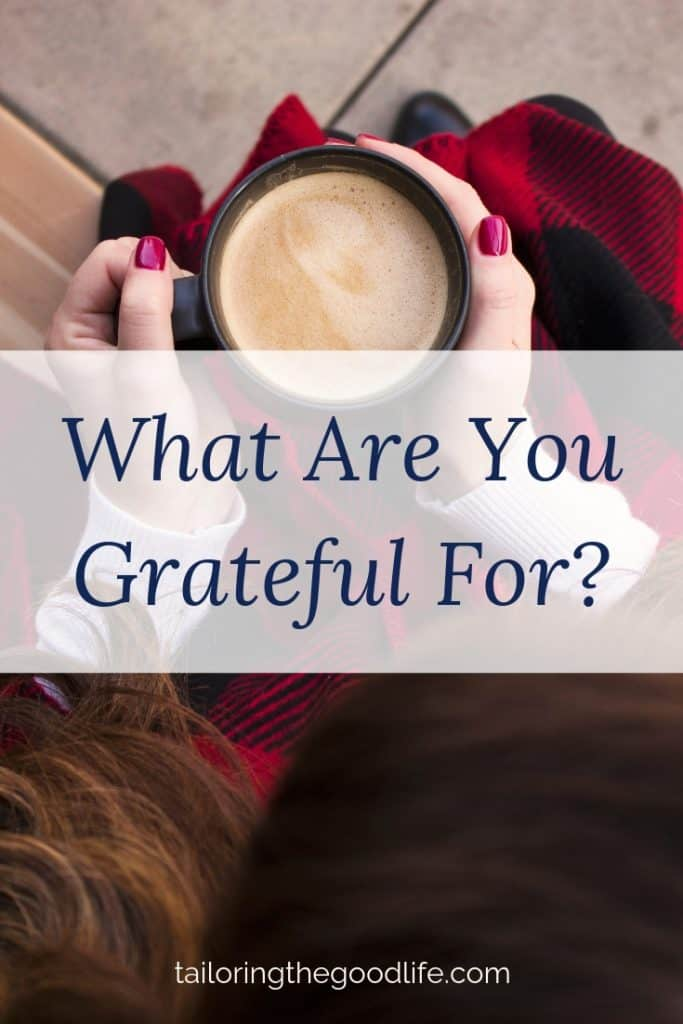 lady in a cozy dark red scarf with a cup of coffee thinking about gratitude journal prompts