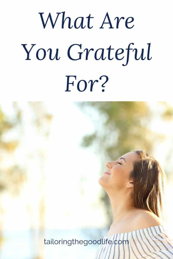 smiling woman looking up with her eyes closed thinkg about gratitude journal prompts